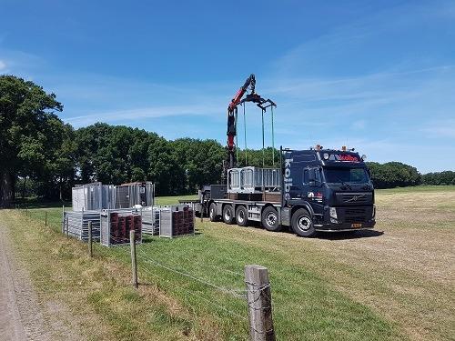 Vrachtwagen haalt met machine de bouwhekken eraf